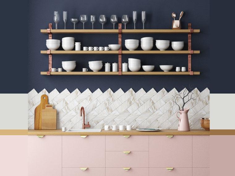 ภาพ: แต่งผนังห้องครัวสีน้ำเงินเข้มขรึมให้อ่อนหวานขึ้นด้วยกระเบื้องลายหินอ่อนขนาดเล็กสีขาว-เทาปูในแนวเฉียง ร่วมกับบานประตูตู้เก็บของสีชมพูอ่อน เพิ่มความน่ารักด้วยมือเปิดบานตู้สีทอง และก๊อกน้ำกับโลหะชั้นวางของสีทองแดง
